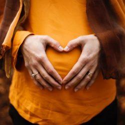Schwangere Frau hält Hände zum Herz geformt vor ihren Bauch